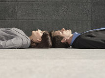 Business People Lying Head To Head On Ground Royalty Free Stock Images