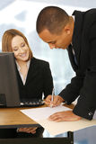 Business People Making A Deal In Office. Business woman looking at business man bend over to sign an empty paper on table. focus on the woman. perfect concept Stock Image