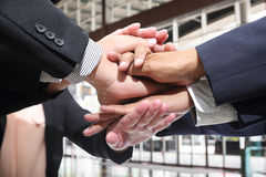 Business people making pile of hands Royalty Free Stock Images