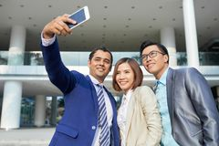 Business people making selfie outdoors. Group of business people in formal wear standing together outdoors near the office building and posing at camera of stock images
