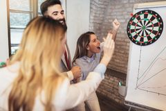 Business people making team training exercise during team building seminar, play darts. Indoor team building activities royalty free stock photo