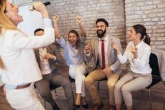 Business people making team training exercise during team building seminar singing karaoke. Having fun stock image