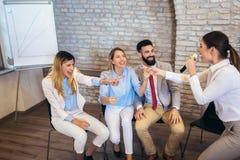 People making team training exercise during team building seminar singing karaoke. Indoor team building activities. Business people making team training exercise stock images