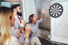 Business people making team training exercise during team building seminar, play darts. Indoor team building activities stock photos