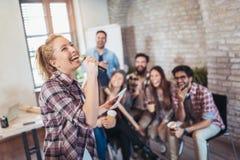 Business people making team training exercise during team building. Seminar singing karaoke royalty free stock image