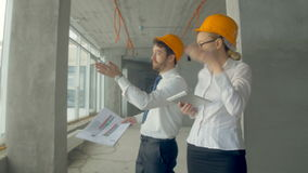 Business people, man and woman discussing construction plan, walking at a construction site. Steadycam shot. Close up. Business people, man and woman discussing stock footage