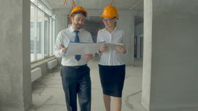 Business people, man and woman discussing construction plan, walking at a construction site. Steadycam shot. Business people, man and woman discussing stock video