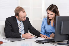 Business people - man and woman in a meeting - talking about fin Royalty Free Stock Photography
