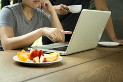 Business people man and woman team work with laptop with fresh f. Ruit on the table stock photo