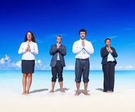 Business people meditating on the beach Stock Images