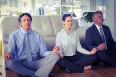 Business people meditating in lotus pose Stock Photos
