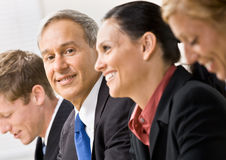 Business people in meeting. Man looks at the camera while in a business meeting Stock Image