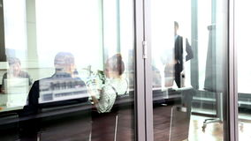 Business people on a meeting behind glass wall stock footage
