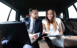 Man and woman discussing work documents in taxi Stock Images
