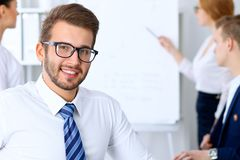 Business people at meeting in office. Focus at cheerful smiling bearded man wearing glasses. Conference, corporate. Business people at meeting in office. Focus stock photo