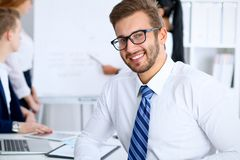 Business people at meeting in office. Focus at cheerful smiling bearded man wearing glasses. Conference, corporate. Training or brainstorming of people group stock photos