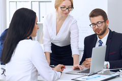 Business people at a meeting in the office. Focus on woman pointing into laptop Royalty Free Stock Image