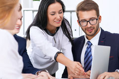 Business people at a meeting in the office. Focus on woman pointing into laptop Royalty Free Stock Photography