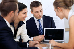 Business people at  meeting in the office. Focus on woman pointing into laptop Stock Photo