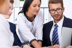 Business people at a meeting in the office. Focus on woman pointing into laptop Stock Photo