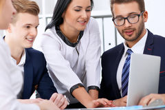 Business people at a meeting in the office. Focus on woman pointing into laptop Royalty Free Stock Photo