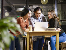 Business people meeting in office. A team asian and caucasian entrepreneurs meeting in office discussing business using laptop computer Royalty Free Stock Image