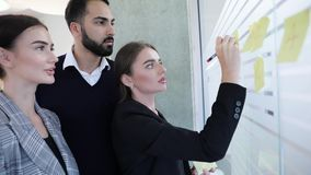 Business people meeting in office. Workers planning strategy. Business People meeting in office. Workers planning project strategy, writing notes on glass wall stock footage