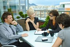 Business people meeting outdoor. Group of young business people sitting around table on office terrace outdoor, talking and working together royalty free stock photography