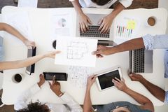 Business people at meeting passing document, overhead shot Royalty Free Stock Image