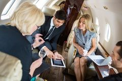 Business People Meeting In Private Jet. Businessman showing project on digital tablet with colleagues in private jet stock photo