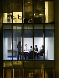 Business People In Meeting Room At Night. View of young businessman with colleagues in meeting room through window at night stock images