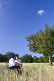 Business people meeting at table in rural field stock photography