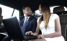 Business People Meeting Working Car Inside. Shot of a handsome confident businessman and partners traveling while working on a laptop sitting in a luxury car in Royalty Free Stock Images