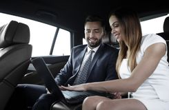 Business People Meeting Working Car Inside. Shot of a handsome confident businessman and partners traveling while working on a laptop sitting in a luxury car in Royalty Free Stock Image