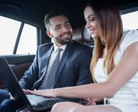 Business People Meeting Working Car Inside. Shot of a handsome confident businessman and partners traveling while working on a laptop sitting in a luxury car in Stock Photos