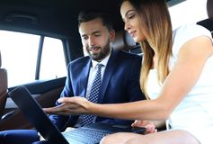 Business People Meeting Working Car Inside. Shot of a handsome confident businessman and partners traveling while working on a laptop sitting in a luxury car in Royalty Free Stock Photography