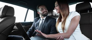 Business People Meeting Working Car Inside. Shot of a handsome confident businessman and partners traveling while working on a laptop sitting in a luxury car in Stock Photography