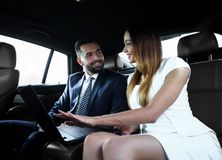 Business People Meeting Working Car Inside. Shot of a handsome confident businessman and partners traveling while working on a laptop sitting in a luxury car in Stock Image