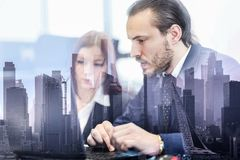 Business people in modern office against new york city manhattan buildings and skyscrapers window reflections. royalty free stock photography
