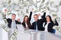 Business people with money rain in conference room