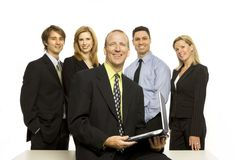 Business people near desk. Five business people stand proudly near a desk Stock Photos