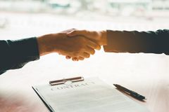 Business People Negotiating A Contract Handshake Between Two Col Royalty Free Stock Photo