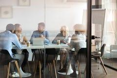 Business people negotiating at boardroom behind closed doors royalty free stock image
