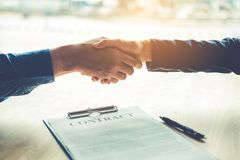 Business people negotiating a contract handshake between two col. Leagues Royalty Free Stock Photo