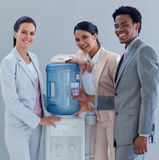 Business people next to a water cooler. Business people speaking next to a water cooler in office Royalty Free Stock Photos