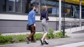 Business people at office building. Back view of business man and woman walking and communicating near urban office. Back view of business man and woman walking stock video footage