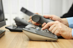 Business people in office calling customers on land line telepho Royalty Free Stock Photo