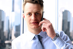 Business, people and office concept - young businessman calling on smartphone over office near with window Stock Photos