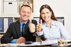 Business people in office holding thumbs up Royalty Free Stock Photo