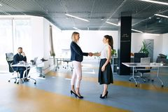 Business people in the office. Two women shaking hands. Stock Image